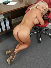 Blonde mature Iris teases her big tits while undressing in her office