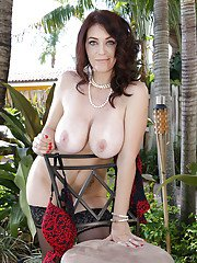 Milf babe Charlee Chase posing outdoors in high heels exposes big tits