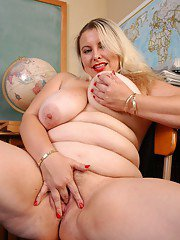 Busty blonde teacher Tawni undressing in classroom to expose bald cunt