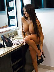 Busty hottie Brook Ultra poses in black stockings and high heels in kitchen