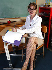 Mature schoolteacher Angelika pulls down fishnet pantyhose to bare pussy