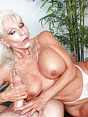 Busty mature woman stroking thick dick for cumshot on large boobs