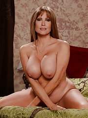 Busty mature housewife Darla Crane doing housework in jeans and bra