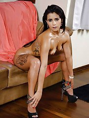 Brunette chick Loren flashing shaved Latina pussy on couch in high heels