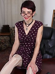 Petite mature woman Nikki Lee posing fully clothed in glasses for nerd look