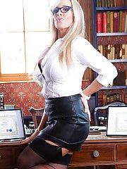 Glasses clad blonde Rebecca Moore flashing panties and garters over desk