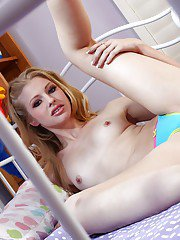 Blonde solo babe Avril Hall posing teasingly on bed in yoga pants