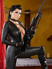Busty babe model Romi Rain looking dangerous in latex outfit with long gun