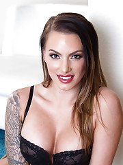 Tattooed Latina wife Juelz Ventura posing on bed in hot black lingerie