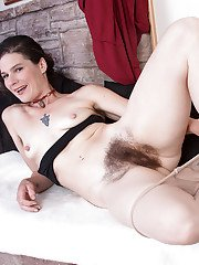 Mature solo model Sunshine rolling pantyhose down to reveal hairy vagina