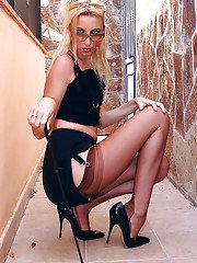Leggy blonde chick with riding crop in hand showing leg and stocking tops
