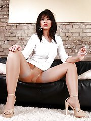 Smoking hot older MILF Desyra Noir having a cigarette on leather couch