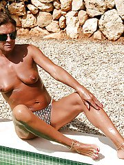 Kinky mature woman Lady Sarah posing outdoors in thong and sunglasses