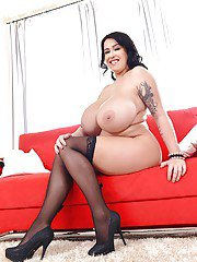 Bosomy brunette tit model Leanne Crow posing topless in stockings