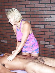 Clothed over 40 blonde chick gives interracial massage and handjob