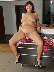 Older redhead with saggy breasts spreading shaved vagina in high heels