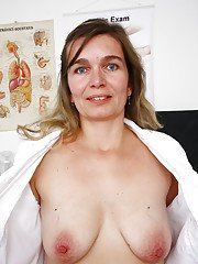 Chubby mature nurse bares saggy tits while inserting speculum in vagina