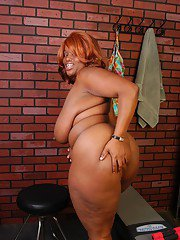 Mature black fatty with large tits slips off panties to expose massive ass