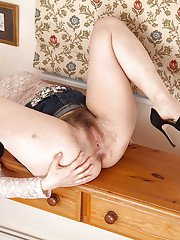 Older lady in high heels and denim skirt showing off exposed pubic hairs
