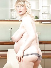 Blonde solo girl Casey Deluxe exposing belly bump and huge tits in kitchen