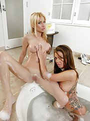 Wet and busty lesbian pornstars humping shaved pussies in bathtub