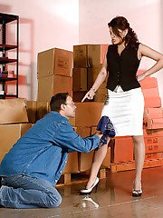 Skirt attired boss woman having legs and barefeet worshiped by man