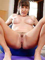 Mature babe Alexandra Silk freeing big tits and beaver from yoga outfit