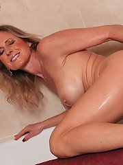 Busty older lady Jade Jamison showing off ass in bath before masturbating