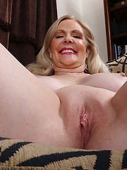 Older blonde female Judy Belkins removing black hose to bare shaved twat