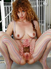 Curly older redhead Leona parting hairy vagina in bodystocking