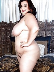 Obese brunette Lucy Lenore freeing large tits from sheer pink lingerie