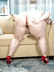 Busty fatty Porsche Dali strips off and masturbates her fat pussy on a sofa