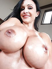 Sexy brunette MILF Jewels Jade revealing oiled hooters and sexy ass