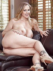 MILF pornstar Julia Ann letting large natural tits free during couch disrobing