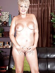 Older housewife Tracy Licks getting naked on leather sofa before masturbating