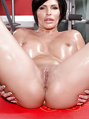 Dark haired MILF Shay Fox letting big fake boobs loose from bra in home gym