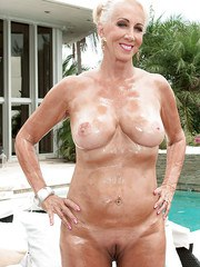 Older blonde woman Madison Milstar tossing bikini aside to show off naked body