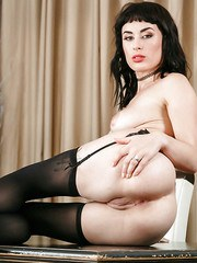 Dark haired female Olive sheds sheer lingerie to model in nylons and garters