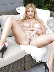Leggy blonde MILF Jazmyn uncovers hooters while removing swimsuit on patio