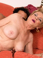 Horny grandma Lin Boyde seducing younger Latino man for sex on chesterfield