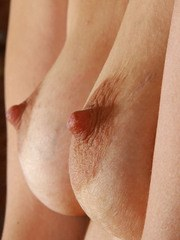 Older solo model Loredana plays with pubic hairs while parting pussy lips