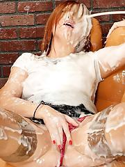 Clothed redhead gets covered in massive amounts of sperm via a glory hole