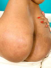 Ebony chick in red heeled shoes shows off her big oiled booty and masturbates