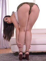Brunette female Nekane slips cutoff shorts and thong panties over juicy ass