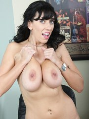 Dark haired MILF Alia Janine unveils her hanging hooters in her office