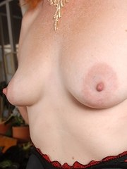 Older redhead removes her dress and pretties to expose the pinkest pussy going