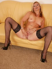 Middle-aged blonde strips to black stockings before playing with her vagina