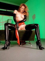 Natural redhead Amber peels off latex ensemble in a sexy manner