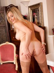 Saucy mature lady Scarlet strips off skirt and blouse to pose in tan nylons