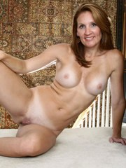 Older woman Crystal plays with her creamy pussy after getting undressed